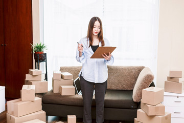 Young woman checklist with cardboard box at home - Business online and delivery concept