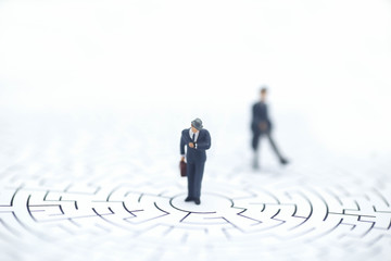Miniature people: Businessman standing on center of maze