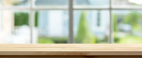 Wood table top inside the house with blur green garden outside window in background, panoramic banner