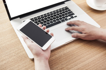 man hand hold a smart phone, notebook with stationary on the wooden desk at the office.
