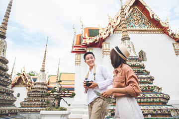 Young Asian photographer tourist with his girlfriend visiting Thai temple in Bangkok  Thailand