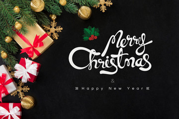 Merry Christmas and Happy New Year text with gift boxes and ornaments on blackboard