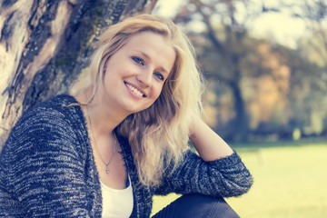 Portrait of smiling blond young woman. Edited as a vintage photo. Horizontally.