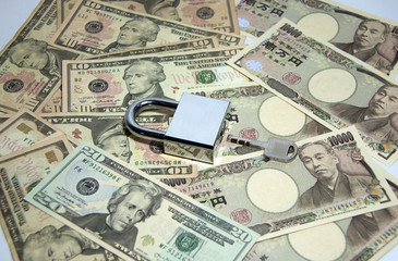 Key to Success of business and finance, The lock and key on the pile of US and Japanese banknotes.