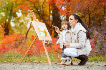 Autumn nature, mom and daughter paint a picture in a park of autumn leaves, painting a Little Child, Child Creativity