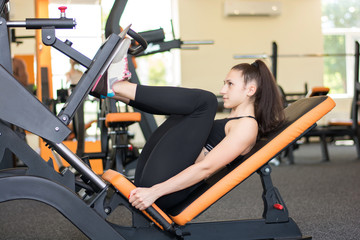 young sportswoman doing fitness exercises for legs muscles in gym