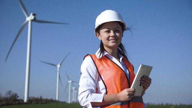 Cheerful woman wearing hard hat standing against turbines at wind farm on sunny day