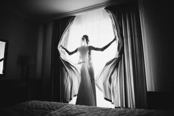 happy luxury stylish brunette bride near a window on the background of vintage room