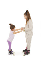 A smiling preschooler on rollerblades. Her sister is holding her hand while trying to encourage her. Isolated on white background
