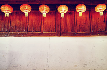 Old wall with Chinese red lanterns, Oriental background with copy space, color toned.