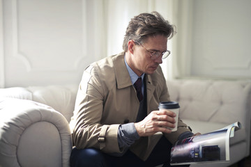 Handsome man drinking coffee while reading a magazine