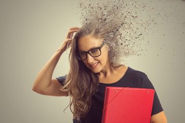 Pensando mulher estudante ou professora com a cebaça desfragmentando isolado no fundo da parede cinza. Menina pensativa que coça a cabeça procurando solucionar um problema