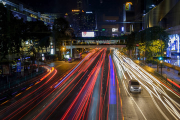 ast and intense traffic in the center of Bangkok at night. Traces from the headlights of cars.