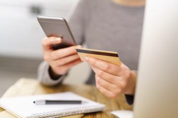 frau hält ihr mobiltelefon und ihre kreditkarte in den händen