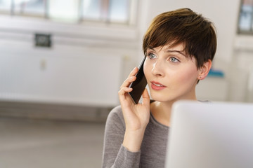 frau telefoniert im büro und schaut zur seite