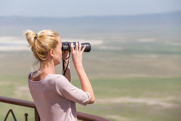 Female tourist looking through binoculars on African safari in Ngorongoro crater consrvation area national park, Tanzania, Afrika.