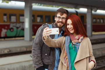 Couple of hipster travelers photographing a selfie with a smartphone in a train station. Travel concept. Mobile photography. Autumn time. Redhair woman and man in glasses