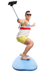 Young man surfing and taking a selfie with a stick