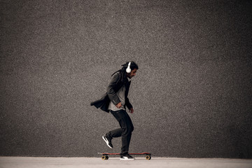 Stylish young dreadlock hipster skater with headphones playing with skate near the grey wall.