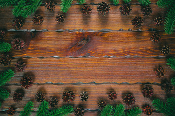 Christmas frame with pine cones, fir branches on wooden brown background. Christmas composition. Top view, free space