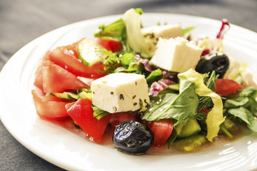 Greek salad with fresh vegetables, feta cheese and olives