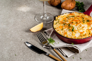 Skillet Shepherd's Pie, british casserole in cast iron pan, with minced meat, mashed potatoes and vegetables, on gray stone background, copy space