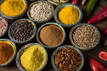 Photo sur Aluminium A selection of various colorful spices on a wooden table in bowls