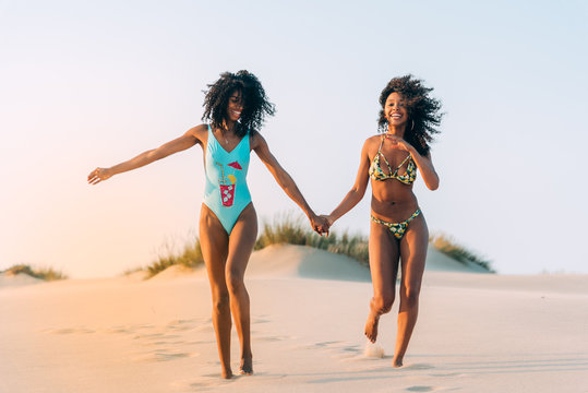Laughing women posing in love on beach