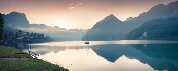 Misty morning panorama of Grundlsee lake. Beautiful summer view of Gessl village, Liezen District of Styria, Austria, Alps. Europe. Artistic style post processed photo.