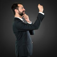 Handsome businessman making tiny sign on black background