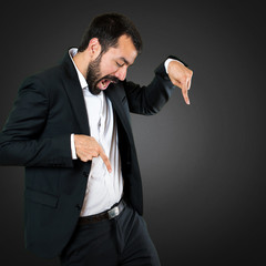 Handsome businessman pointing down on black background