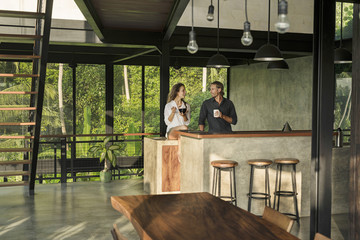 Couple having breakfast and smiling at each other in modern design kitchen with glass facade surrounded by lush tropical garden