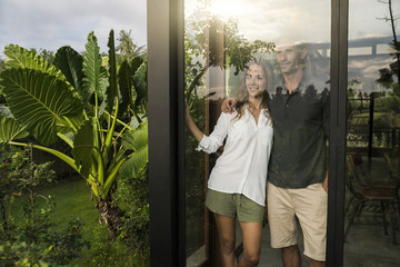 Successful couple looking outside of window of modern design house