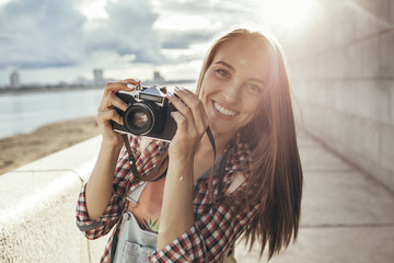 Smiling young woman with a camera at the riverside