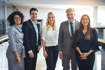 Diverse group of smiling colleagues standing together in an office