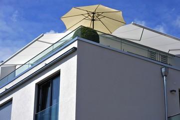 Dachterrasse mit automatischen Markisen und Sonnenschirm auf modernem Wohnhaus