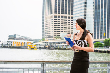 Raining day - grainy, foggy, drizzly feel. American Woman wearing crop bra top, black skirt, standing by river with high building background in New York, reading blue tablet computer, thinking..
