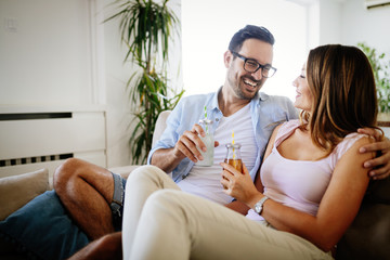 Young happy couple drinking together at home