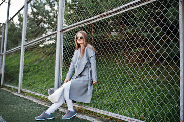 Girl in gray coat with sunglasses at small street stadium.
