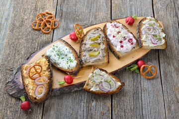 Brotaufstriche auf rustikalem Bauernbrot: Griebenschmalz, Obatzda, Schnittlauchquark, Preiselbeer-Meerrettich-Quark und Landleberwurst -  Hearty Bavarian snack: various spreads on dark farmhouse bread