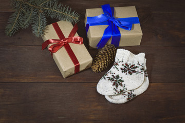 Packed gifts with red and blue ribbons, socks ornament, spruce branch, fir cone