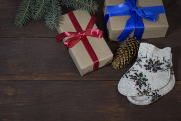 Packed gifts with kraft paper with red and blue ribbons, children's socks with ornament, spruce branch, fir cone on a wooden background