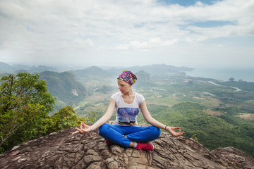 Young woman practicing yoga and meditation in mountains during luxury yoga retreat in Thailand, Asia