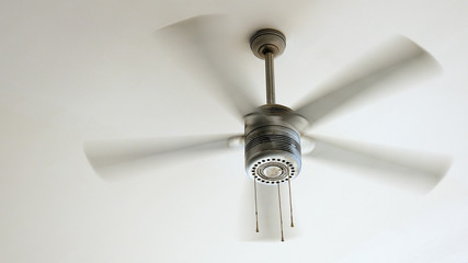 Ceiling fan is rotating at the ceiling of the room. Electric climate equipment.