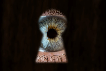 Female blue eye looking through the keyhole. Concept of voyeurism, curiosity, Stalker, surveillance and security