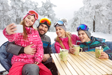 Girl with parents and brother making selfie at winter holiday