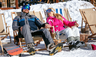 Couple at mountains in winter laughing and relax in sunbed