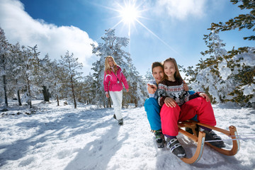 girl and boy enjoying sleigh ride. Child sledding. Toddler kid riding a sledge