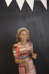 Smiling young woman standing against black background