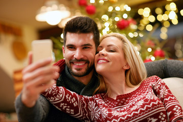 romantic couple taking selfie picture with smartphone at home.